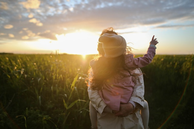 "Photo to illustrated the article ""Adoptions from the heart"", showing a mother with a child on her back, looking at the horizon with the sun, surrounded by grass"