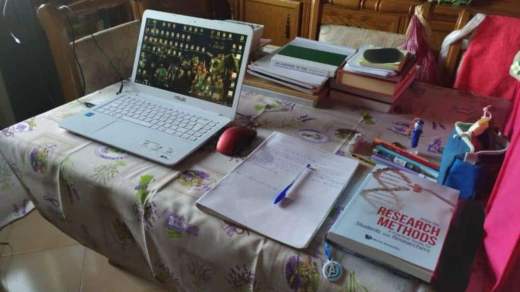Image is a photo of a portion of my minimalist workspace: my living room table with my laptop, notebooks and pens, various books that I need and a box containing other things I might need