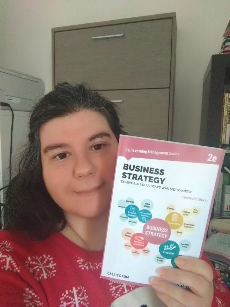 Business Strategy Essentials You Always Wanted to Know: Me (Luana Spinett) holding the book in my left hand, posing with it in the photo